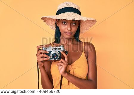 Young african american woman wearing summer hat holding vintage camera relaxed with serious expression on face. simple and natural looking at the camera.