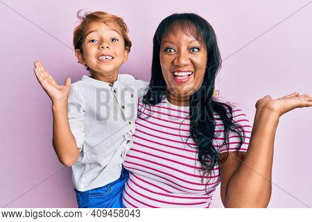 Hispanic family of mother and son hugging together with love celebrating victory with happy smile and winner expression with raised hands