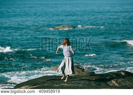 Dancer woman is engaged in choreography on the rocky coast of the Atlantic ocean.