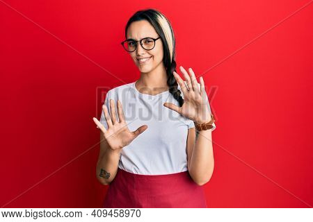 Young hispanic woman wearing professional waitress apron disgusted expression, displeased and fearful doing disgust face because aversion reaction. with hands raised