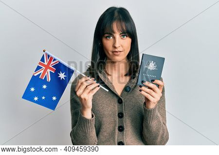 Young hispanic woman holding australian flag and passport relaxed with serious expression on face. simple and natural looking at the camera.