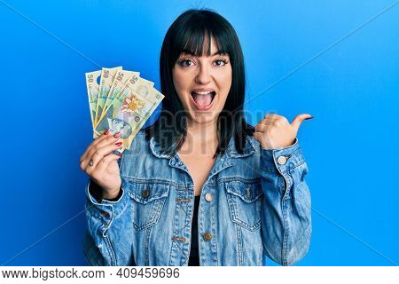 Young hispanic woman holding 50 romanian leu banknotes pointing thumb up to the side smiling happy with open mouth