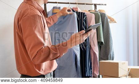 Asian Business Owner Working At Home With Packing Box Of His Online Store Prepare To Deliver Product