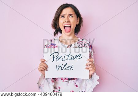 Young beautiful girl holding positive vibes banner angry and mad screaming frustrated and furious, shouting with anger looking up.