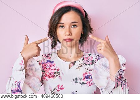 Young beautiful woman pointing with fingers to herself relaxed with serious expression on face. simple and natural looking at the camera.
