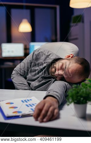 Manager Napping On Desk Because Of Overwork In Workplace. Workaholic Employee Falling Asleep Because