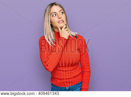 Beautiful blonde woman wearing casual clothes thinking worried about a question, concerned and nervous with hand on chin