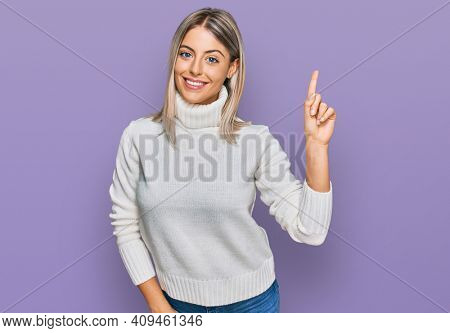 Beautiful blonde woman wearing casual turtleneck sweater showing and pointing up with finger number one while smiling confident and happy.