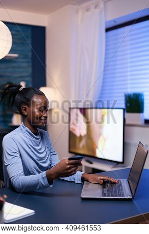 Dark Skinned Woman Making Online Transaction Using Plastic Credit Card Sitting At Desk In Home Offic