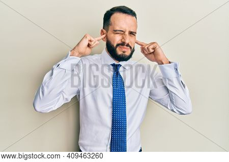 Young man with beard wearing business tie covering ears with fingers with annoyed expression for the noise of loud music. deaf concept.