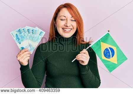 Beautiful redhead woman holding 100 brazilian real banknotes and brazil flag smiling and laughing hard out loud because funny crazy joke.