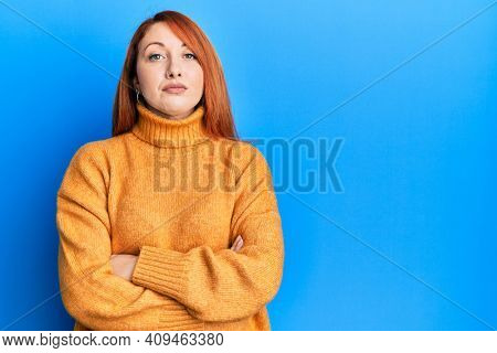 Beautiful redhead woman with arms crossed gesture relaxed with serious expression on face. simple and natural looking at the camera.