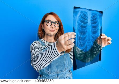 Beautiful redhead woman holding chest radiography smiling looking to the side and staring away thinking.