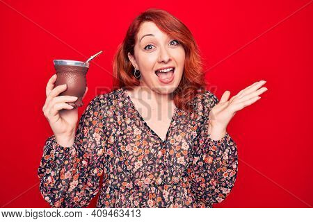 Young beautiful redhead woman drinking mate infusion beverage over isolated red background celebrating achievement with happy smile and winner expression with raised hand