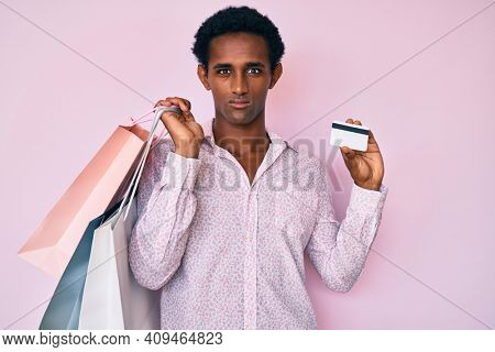 African handsome man holding shopping bags and credit card relaxed with serious expression on face. simple and natural looking at the camera.