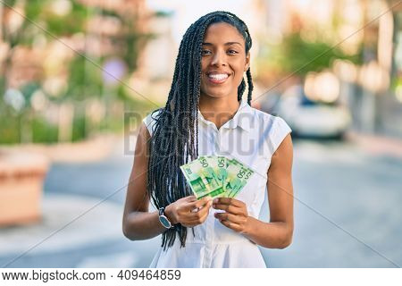 Young african american woman smiling happy holding norwegian 50 krona banknotes at the city.