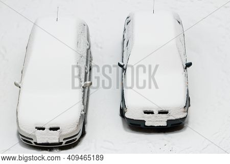 Two Parked Cars Stand In A Snowy Parking Lot And Are Covered With Snow. A Snowstorm Struck. The Cars