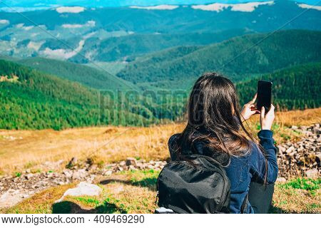 Faceless Girl Taking Photos In Mountains. Back View Of Woman Blogger In Mountain Hiking. Tourist Tra