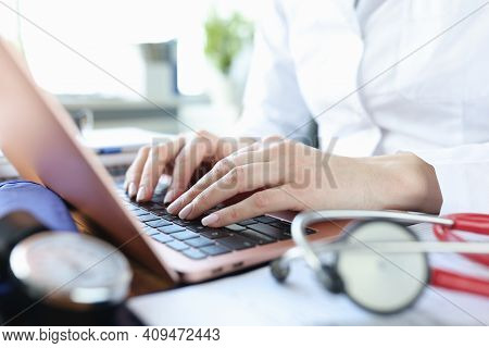Hands Of Doctor Working On Laptop Lie Next To Stethoscope. Therapist Services Concept