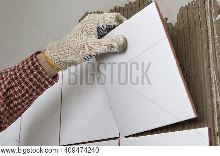Tiler installing ceramic tiles on a wall