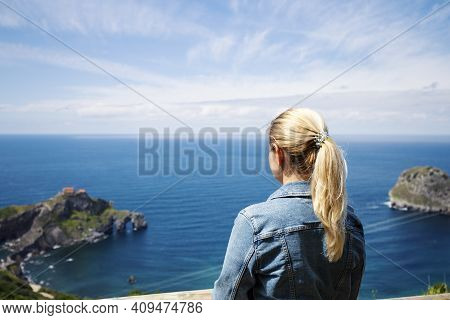 A Lonely Blonde In A Denim Jacket Looks At The Sea And Rocks In The Bay Of Biscay, Spain. Selective