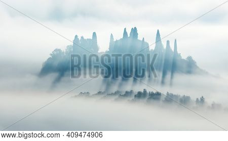 Silhouette of foggy valley - Minimalistic Artistic foggy panoramic landscape at the morning time, trees and hills in fog, light and dark. Tuscany, Italy