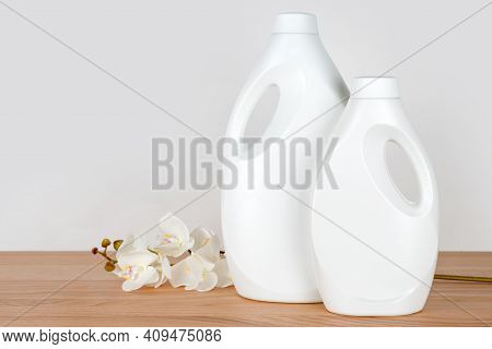 Bottles Of Detergent And Fabric Softener With White Orchid Flowers On Wooden Table. Containers Of Cl