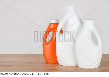 Bottles Of Detergent And Fabric Softener On Wooden Table. Containers Of Cleaning Products. Liquid De
