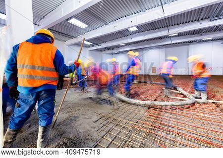 Workers do concrete screed on floor with heating in a new warehouse and office building. Interior finishing industry.