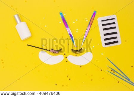 Eyelash Extension Tools And Artificial Eyelashes On A Yellow Background. The View From The Top.