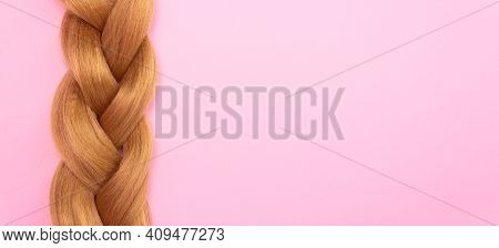 Braid Of Light Brown Artificial Hair On A Pink Background, Free Space For Text. The Concept Of A Hai