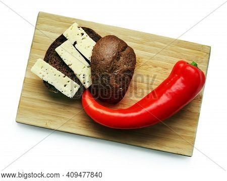 Still Life With Red Ramiro Pepper, Brown Bread And Cheese Slices On The Wooden Cutting Board Against