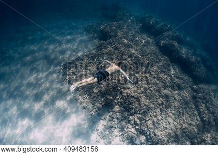 Male Free Diver Glides Underwater In Blue Ocean In Hawaii