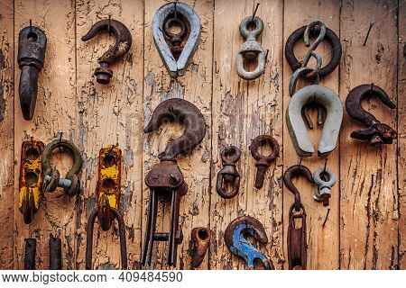 Worn Metal Industrial Pulleys And Hooks Attached To An Old Wooden Shed.