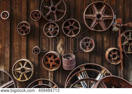 Worn Metal Industrial Wheels Attached To An Old Wooden Shed.