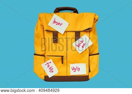 Gorizontal. Bullying. Cyberbullying. Yellow Backpack With Offensive Notes. Loser. Ugly. Fatty. Kick