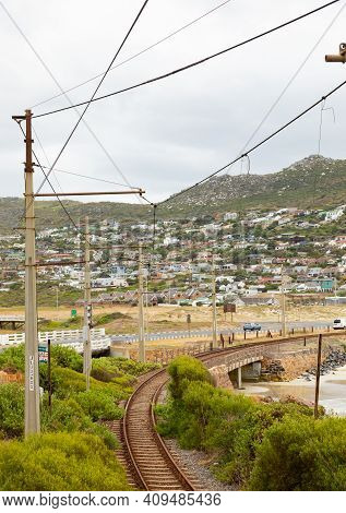 Cape Town, South Africa - February 21, 2021: Electric Passenger Railway Line On The Shoreline Of Gle