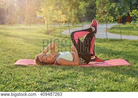 Sporty Little Girl Lying On Toga Mat In Park