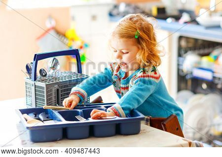 Cute Little Toddler Girl Helping In The Kitchen With Dish Washing Machine. Happy Healthy Blonde Chil