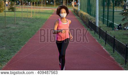 Sporty Little Girl In Face Mask Running In Park