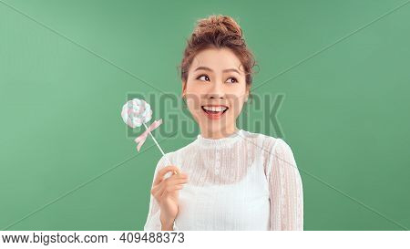 Surprised Curly Girl Eating Lollipop. Beauty Model Woman Holding Pink Sweet Colorful Lollipop Candy,