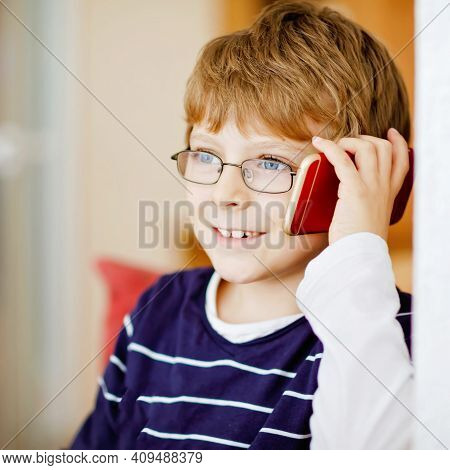 Cute Little Kid Boy Wearing Eye Glasses Speaking On Cellular Phone. Adorable Healthy Child Holding S