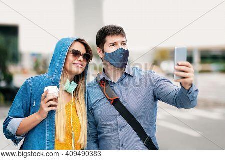 Happy Boyfriend And Girlfriend Having Fun Taking Selfie With Face Mask On City Street - Millenial Ma