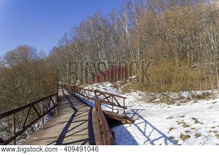 A Footbridge At The Bottom Of A Ravine In A Forest Park. Moscow, Russia. A Sunny Day In Early Spring