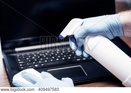 Coronavirus COVID-19 sanitize cleaning disinfection of work desk.Office sanitizing wipe wiping laptop with disinfecting wipes.