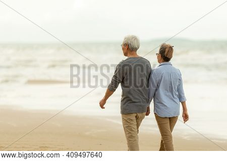 Asian Lifestyle Senior Couple Walking Chill On The Beach Happy In Love Romantic And Relax Time. Peo