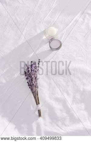 Balsam With Lavender Essential Oil And Dry Flowers On White Bedclothes. Scent Of Lavender Improves S