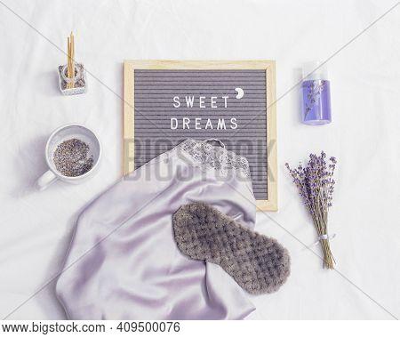 Sleep Mask, Silk Pajamas, Aroma Balsam, Dry Lavender Flowers On White Bedclothes. Wishing You Sweet