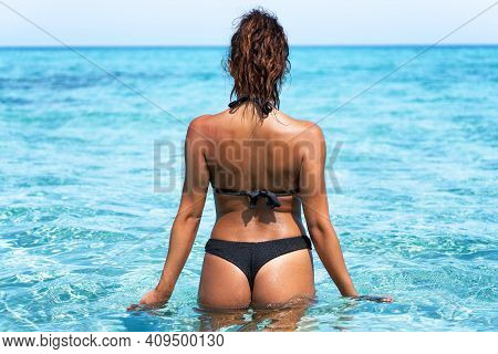 A Beautiful Tanned Girl In A Bikini Shot From Behind Is Having Fun In A Crystal Clear Sea. Perfect S