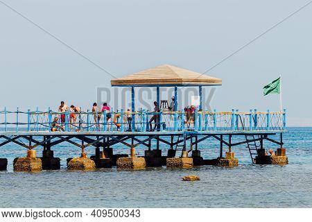 Hurghada, Egypt - October 09, 2010. Tourists Are Walking On Wooden Pier Over Red Sea. Coastal Sunset